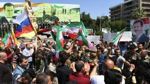 Os sírios agitam as bandeiras russas e iranianas e carregam retratos do presidente Bashar Al Assad em Aleppo. Crédito: George Ourfalian / AFP/ thenational.ae