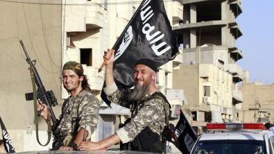 Combatentes militantes islâmicos acenam bandeiras enquanto participam de um desfile militar pelas ruas da província de Raqqa, no norte da Síria, em 30 de junho de 2014 Crédito: Reuters/ Russia Today