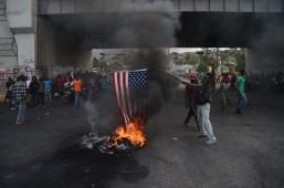 Manifestante queimando bandeira estadunidense no dia 16 de fevereiro. Crédito: Hector Retamal AFP/El Pais