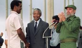 O boxeador Teofilo Stevenson cumprimenta Nelson Mandela, observado pelo ex-presidente de Cuba Fidel Castro, em uma visita do ex-presidente sul-africano à ilha em 1991. Crédito: UOL/https://terceirotempo.uol.com.br/